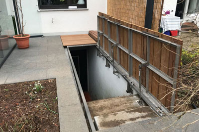 Cover of basement staircase with gas springs